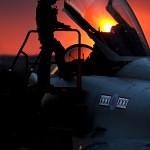 Pilot enters his cockpit as the sun sets